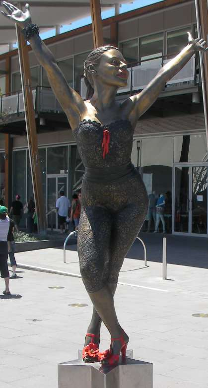 A bronze statue of Kylie, on a star-shaped pedestal, portrays her in a dancing pose. Her legs are crossed and she bends at the waist, with both arms stretched above her head. The statue stands in a public square in front of a modern glass building, and several people are walking.