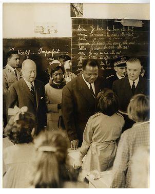 Hubert Maga de la République du Dahomey et madame rendant une visite à une école de Torcy. Sur la gauche sur la photo, Jacques Foccart, Secrétaire général à la présidence de la République pour les affaires africaines et malgaches. Sur la droite, Guy Chavanne, maire de Torcy.