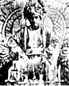 black and white photograph of a young cleanshaven man wearing an elaborate headdress and sitting on a throne. He is wearing robes and in front of him are some accoutrements on a table.