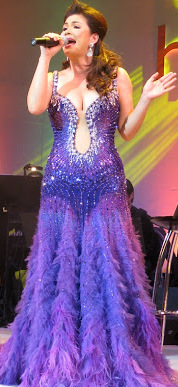 Velasquez wearing a blue gown while singing