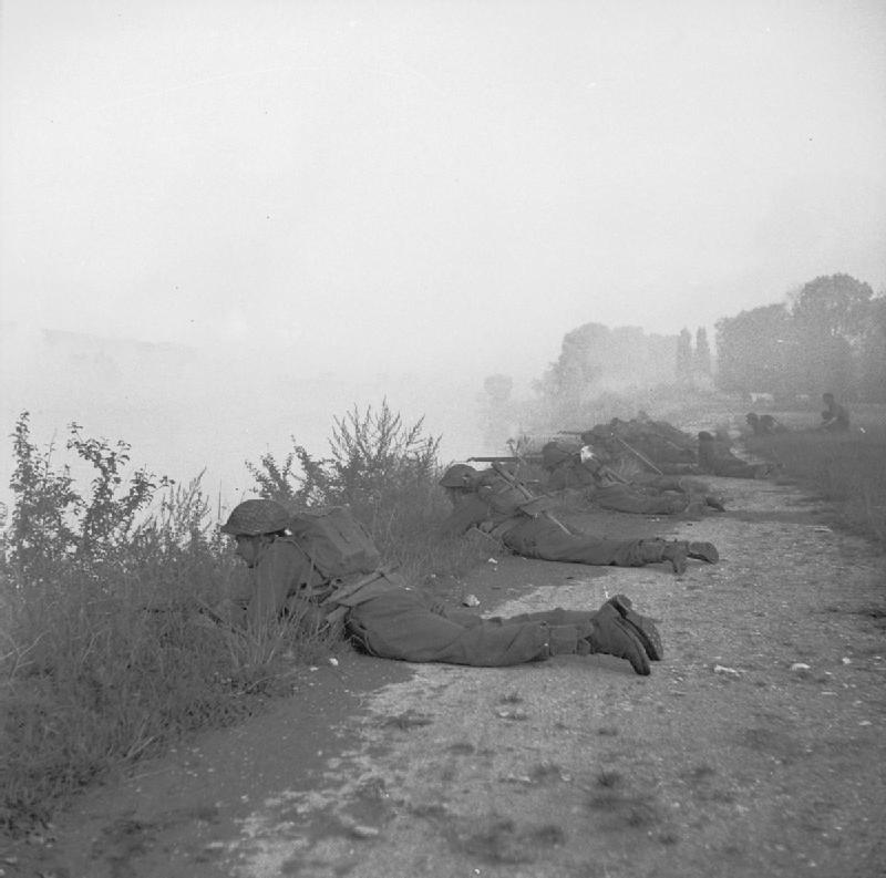 Soldiers lie on the banks of the Seine