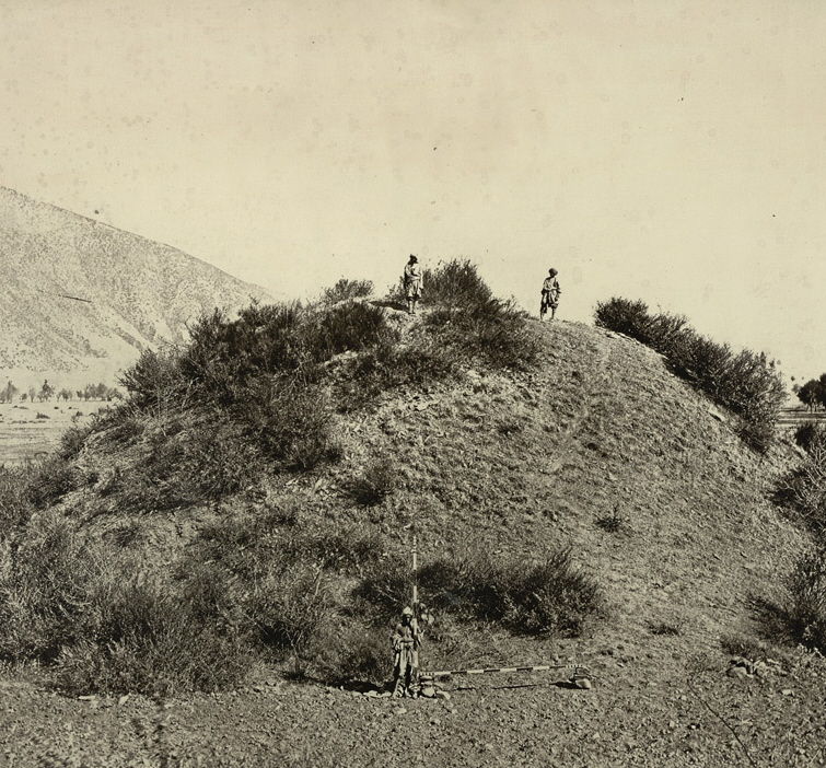This general view of the unexcavated Buddhist stupa near Baramulla, with two figures standing on the summit, and another at the base with measuring scales, was taken by John Burke in 1868. The stupa, which was later excavated, dates to 500 AD.