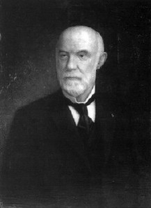 A man in his late fifties, bald on top, with white hair on the sides and a white beard and mustache. He is wearing a black coat and tie and white shirt and facing left