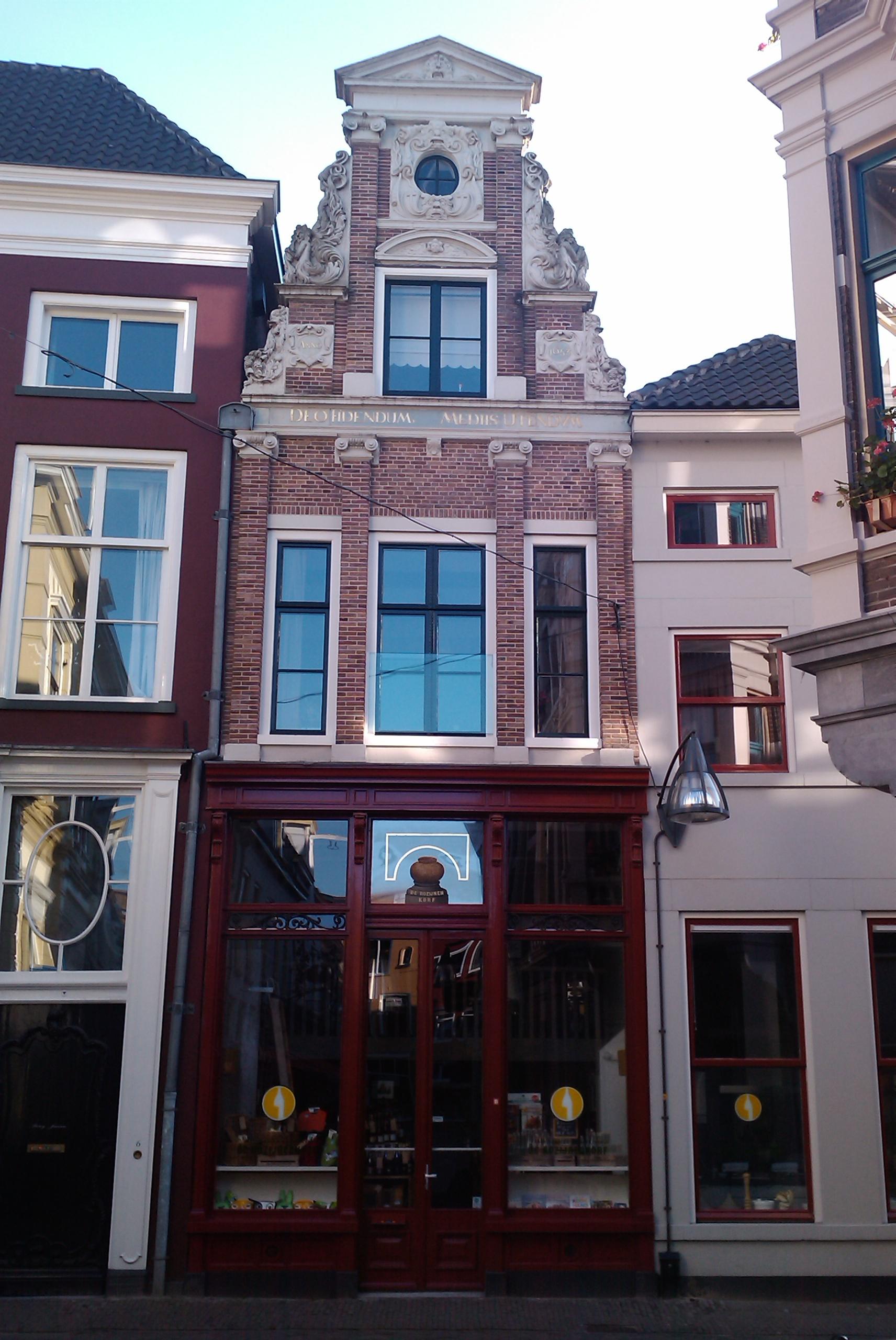 De rozijnenkorf huis met rijk van beeldhouwwerk voorziene halsgevel winkelpui uit 1900 na een - Gerenoveerd huis voor na ...