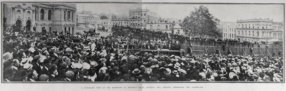 Panoramic view of a large crowd assembled in front of group of speakers