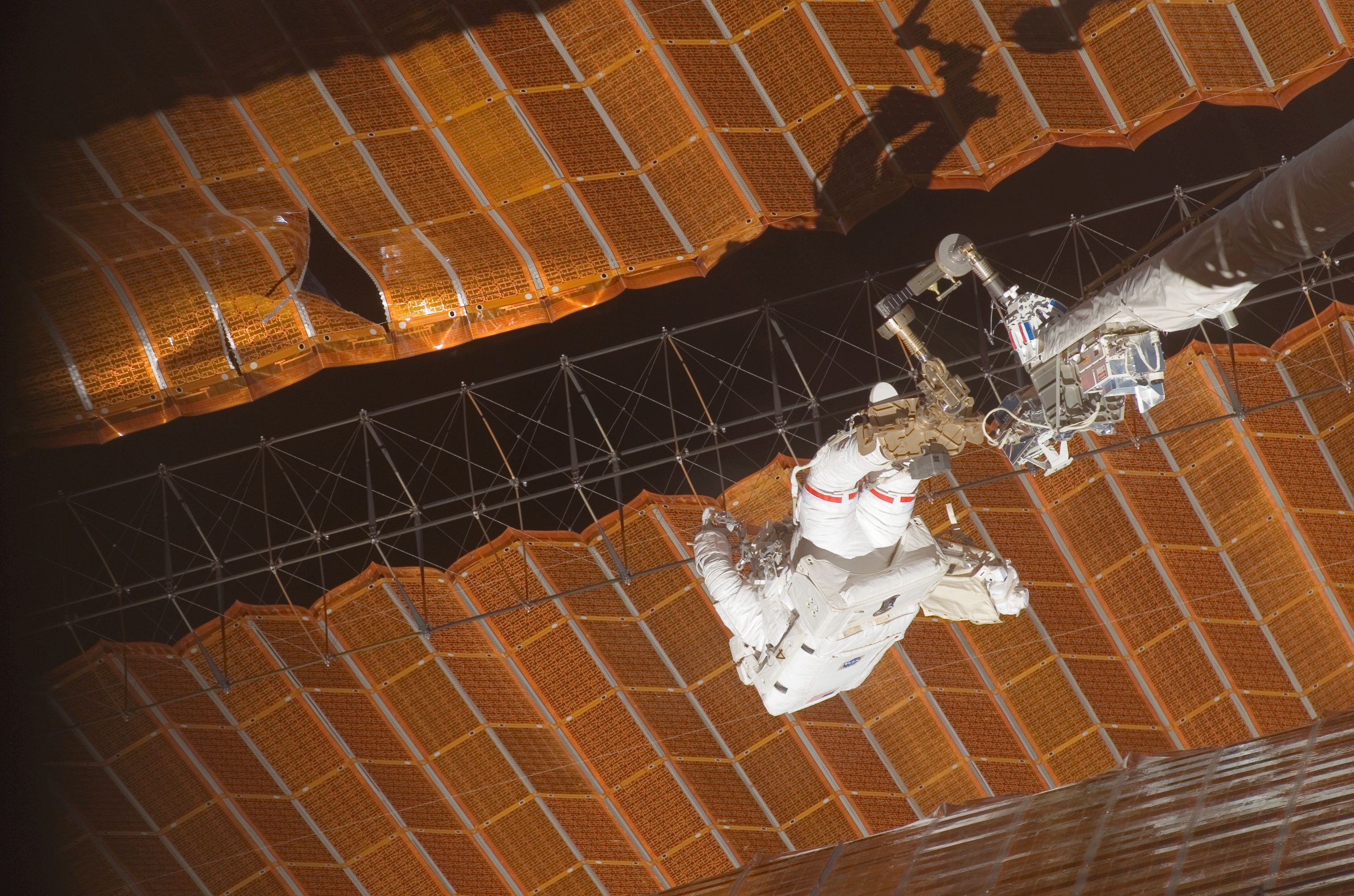 Two black and orange solar arrays, shown uneven and with a large tear visible. A crew member in a spacesuit, attached to the end of a robotic arm, holds a latticework between two solar sails.