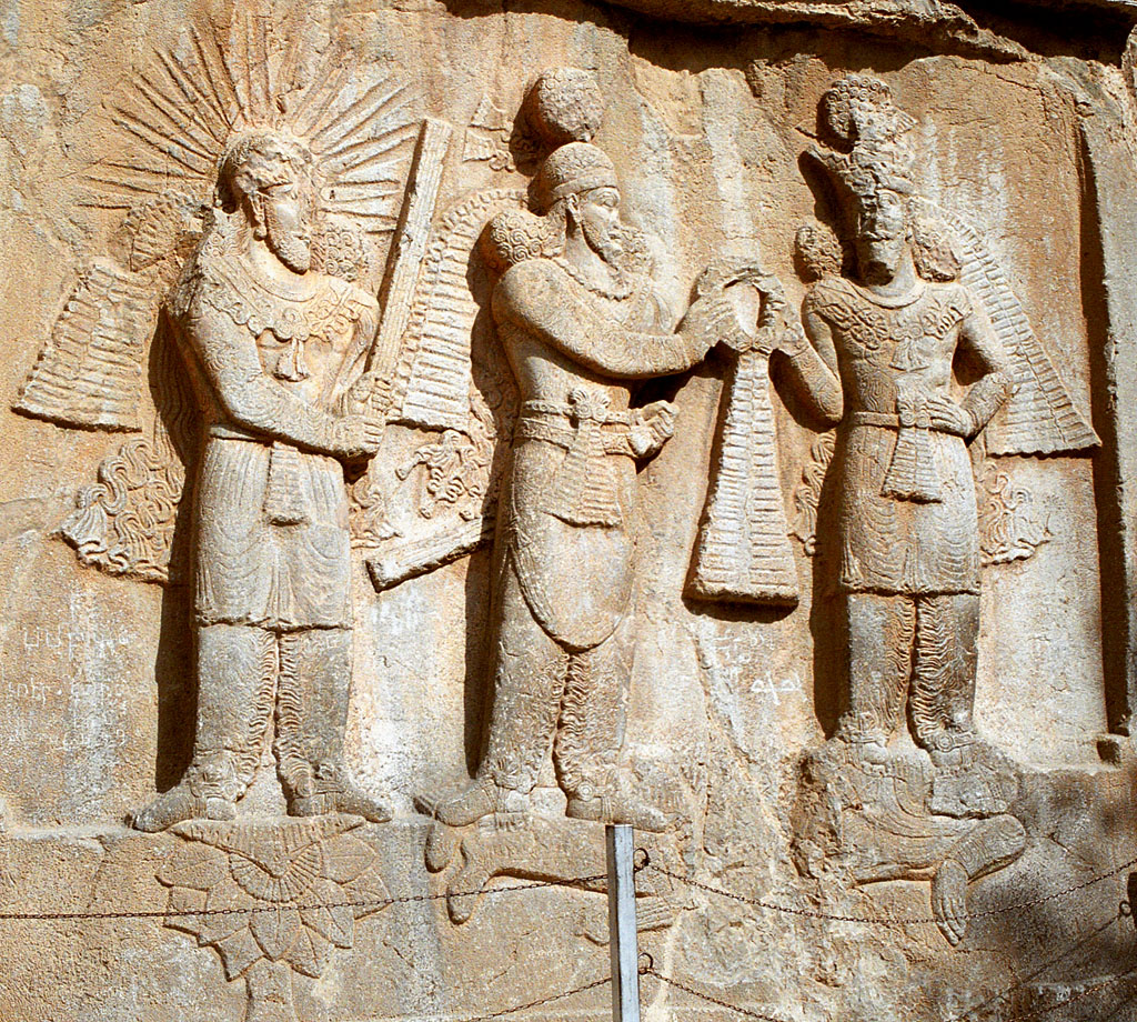 Investiture of Sassanid emperor Ardashir I or II (3rd century CE bas-relief at Taq-e Bostan, Iran. On the left stands the yazata Mithra with raised barsom, sanctifying the investiture.
