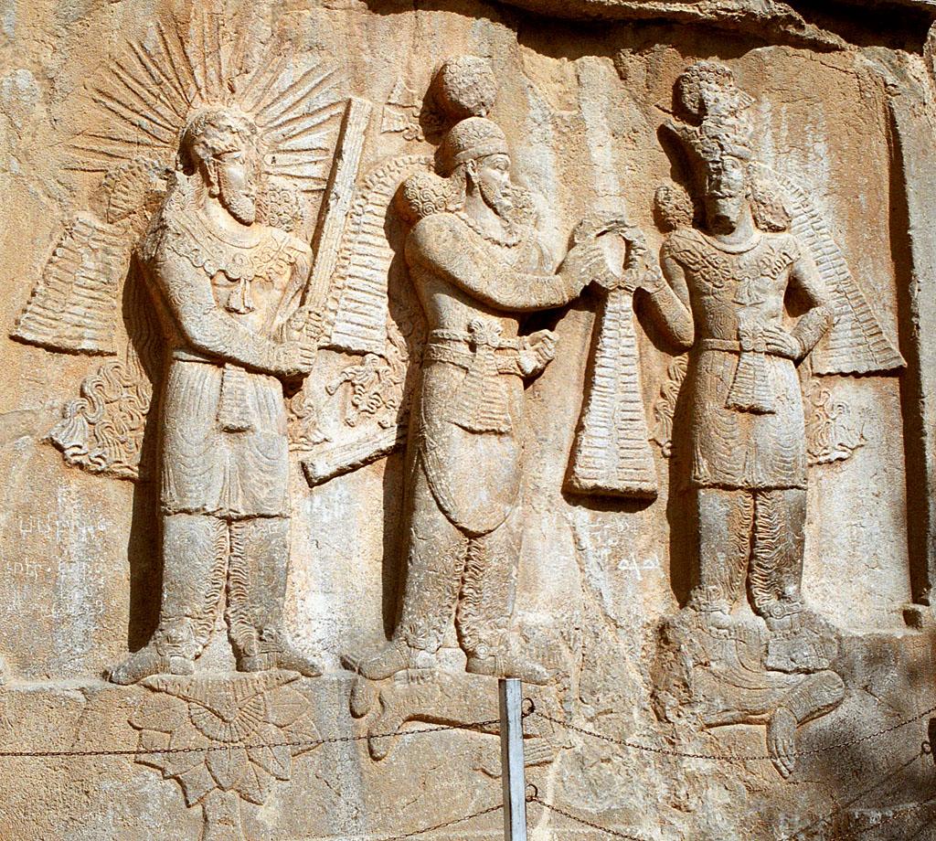 نقشی از تاق بستان در کرمانشاه ایران. در این نقش شاه ساسانی شاپور دوم در میان و در سمت چپ وی اهورا مزدا که حلقه فرایزدی را برای تاجگذاری به او میدهد، بر روی دشمنی به خاک افتاده (ژولیان امپراتور روم) ایستادهاند. درسمت راست شاه، میترا یا مهر، که پیکانهای نوری همچون خورشید از سر او در همهٔ سمتها پراکنده شده، شاخهای از گیاهان به نام «برسم» را در دست گرفتهاست و بر روی گل نیلوفری ایستادهاست.