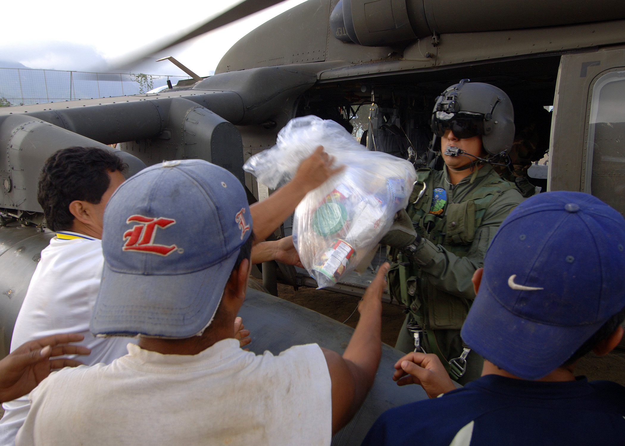A helmeted soldier hands out bags of supplies