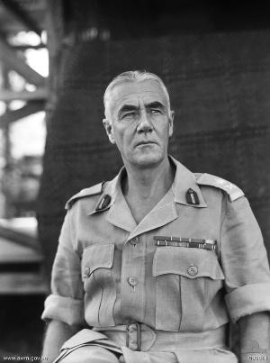 Grey-haired man in Army shirt with sleeves rolled up. He is wearing rank badges and ribbons but no tie or hat.