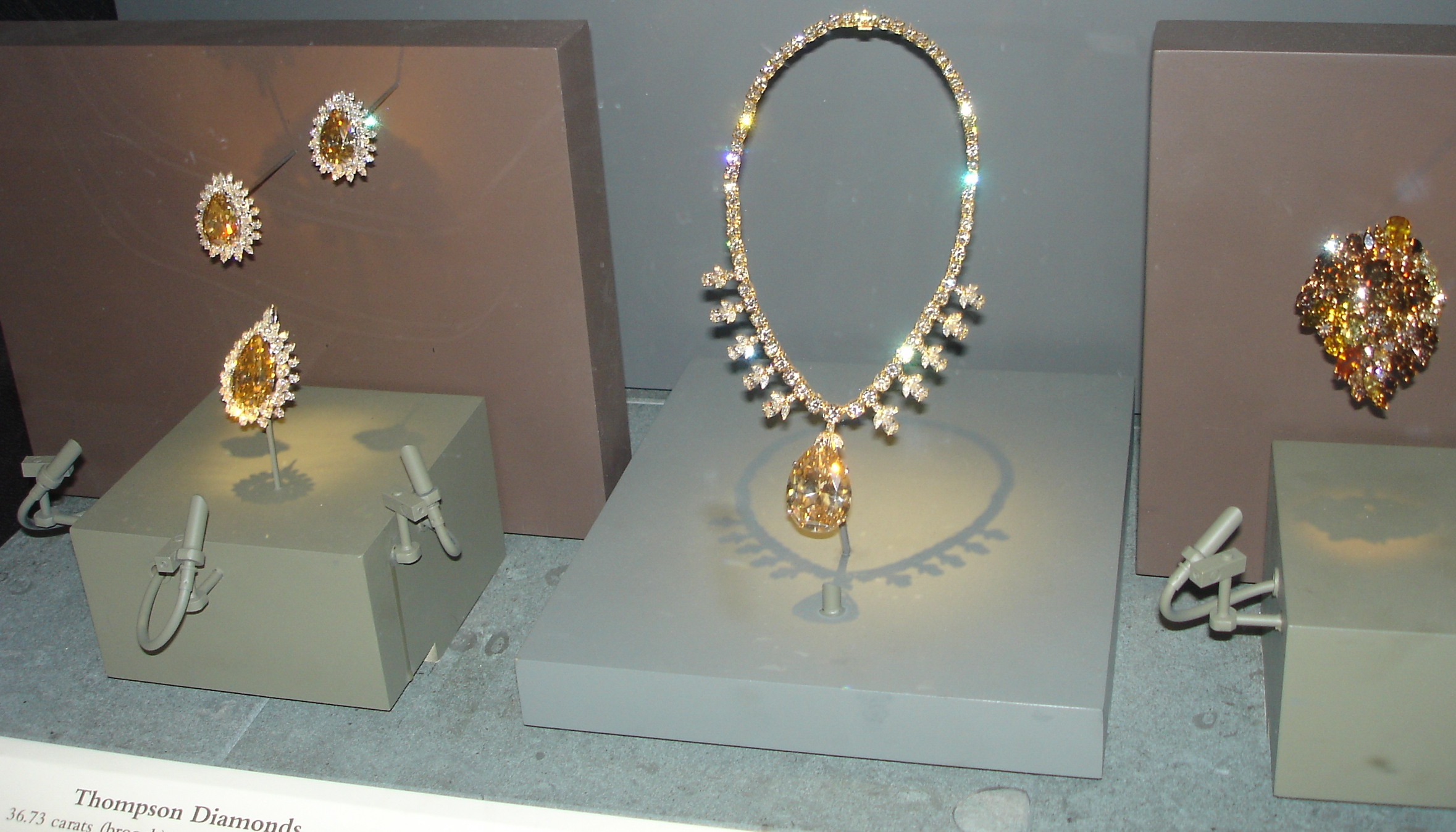 A museum display of jewelry items. Three brooches each consist of a large brown central gem surrounded by many clear small stones. A necklace has a large brown gem at its bottom and its string is all covered with small clear gems. A cluster-shaped decoration contains many brown gems.
