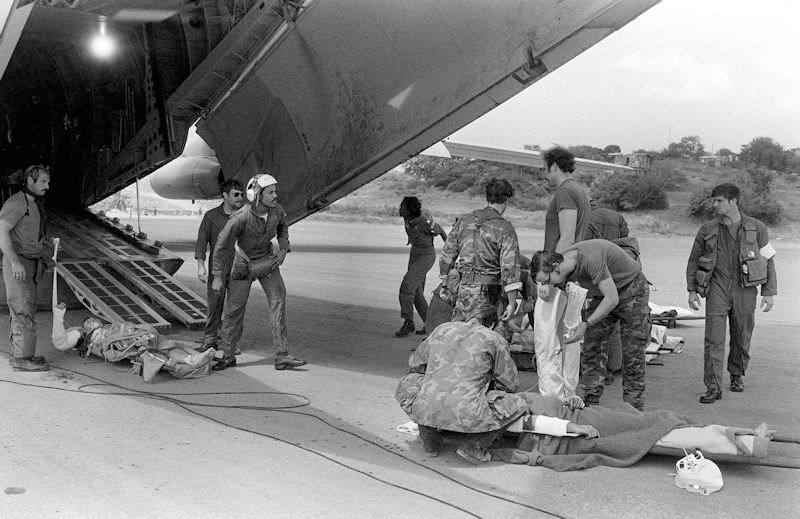 A wounded soldier is treated by U.S. military personnel before being placed aboard a C-141B Starlifter aircraft for medical evacuation during Operation Urgent Fury in Grenada