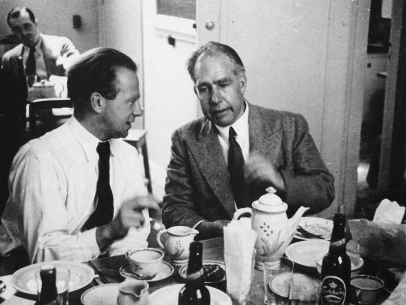 A young man in a white shirt and tie and an older man in suit and tie sit at a table, on which there is a tea pot, plates, cups and saucers and beer bottles.