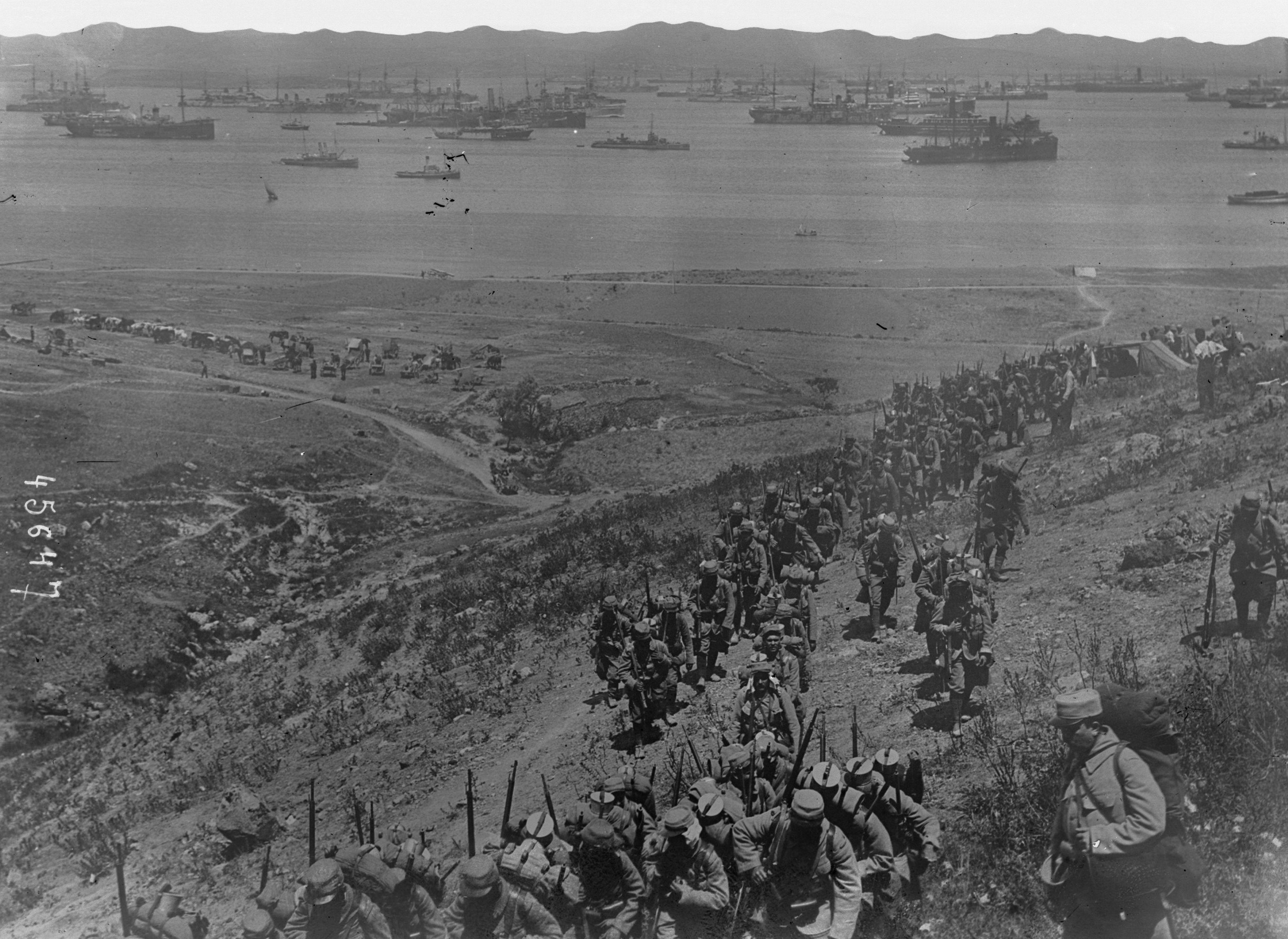 Photographie prise depuis une colline donnant sur une large baie où se trouvent de nombreux navires de transport. Au premier plan, une colonne de soldats en armes marche sur un sentier dans un paysage aride et pelé.