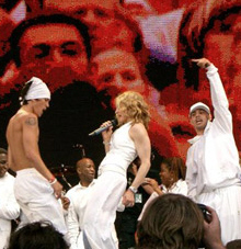 Left profile of a blond female who is singing into a microphone in her right hand. She is wearing white trousers and white, sleeveless overcoat with bangles in her hands. The woman is flanked by two male dancers and behind them another group of people is seen, all dressed in white garments. The backdrop displays blurry faces of the crowd.