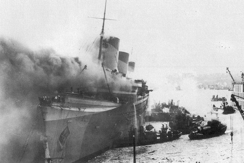El buque SS Normandie, rebautizado USS Lafayette (AP-53), envuelto en llamas en el puerto de Nueva York (9 de febrero de 1942).