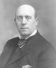 A black-and-white photo of a bald, middle-aged man