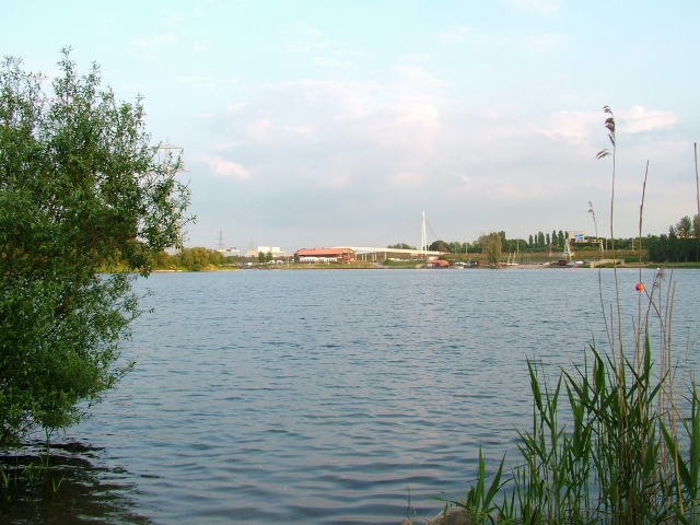 View over Sale Water Park, taken in May 2007, from the north east of the lake, on the edge of Broad Ees Dole, looking towards Deckers. The bridge in the far background, behind the water sports centre and restaurant complex, is a footbridge over the M60.