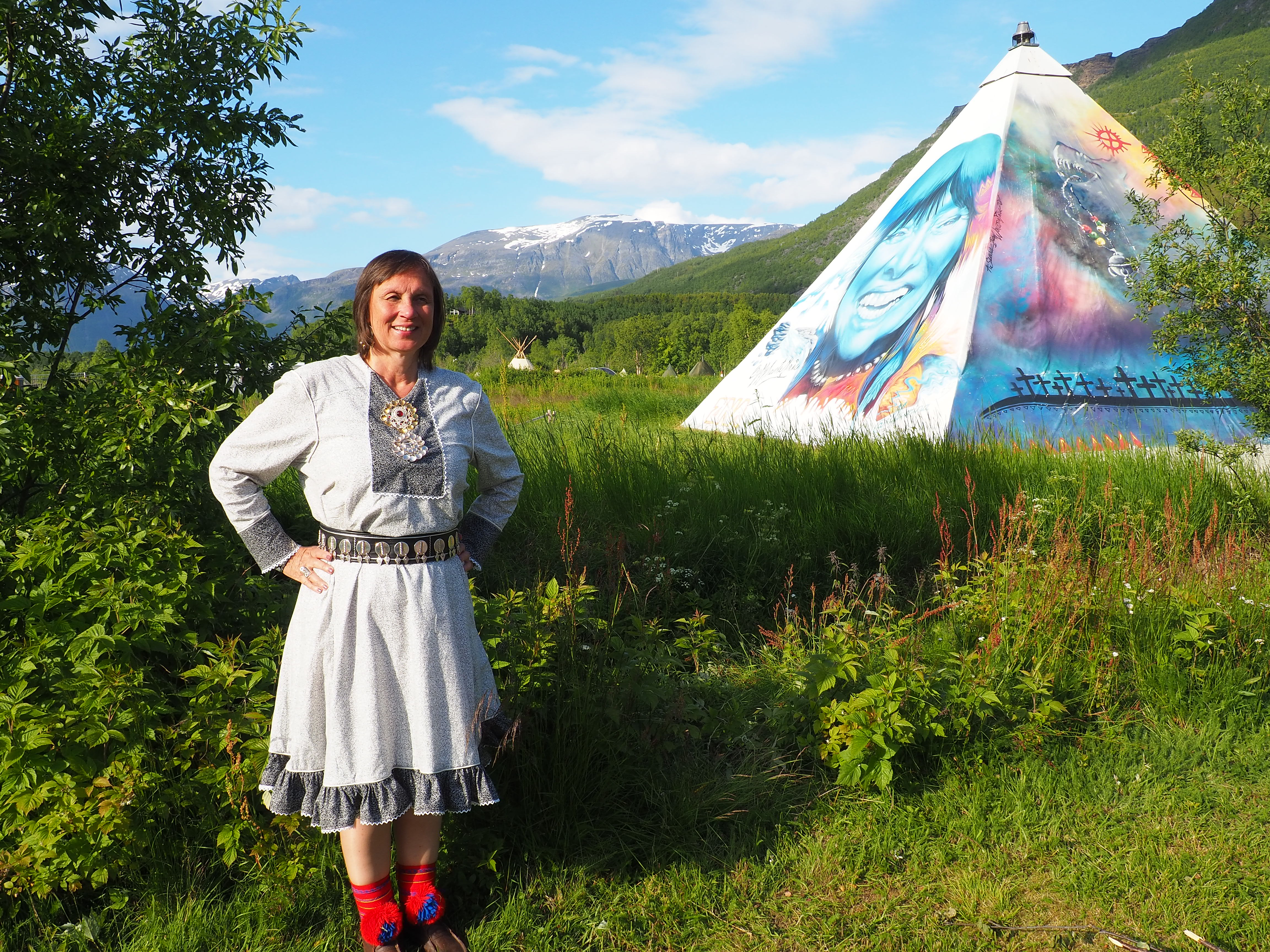 Liv Inger Somby Riddu Riđđu -festivaaleilla Norjassa. Linda Zina Aslaksenin maalaama kuva Buffy Saint-Mariesta taustalla.