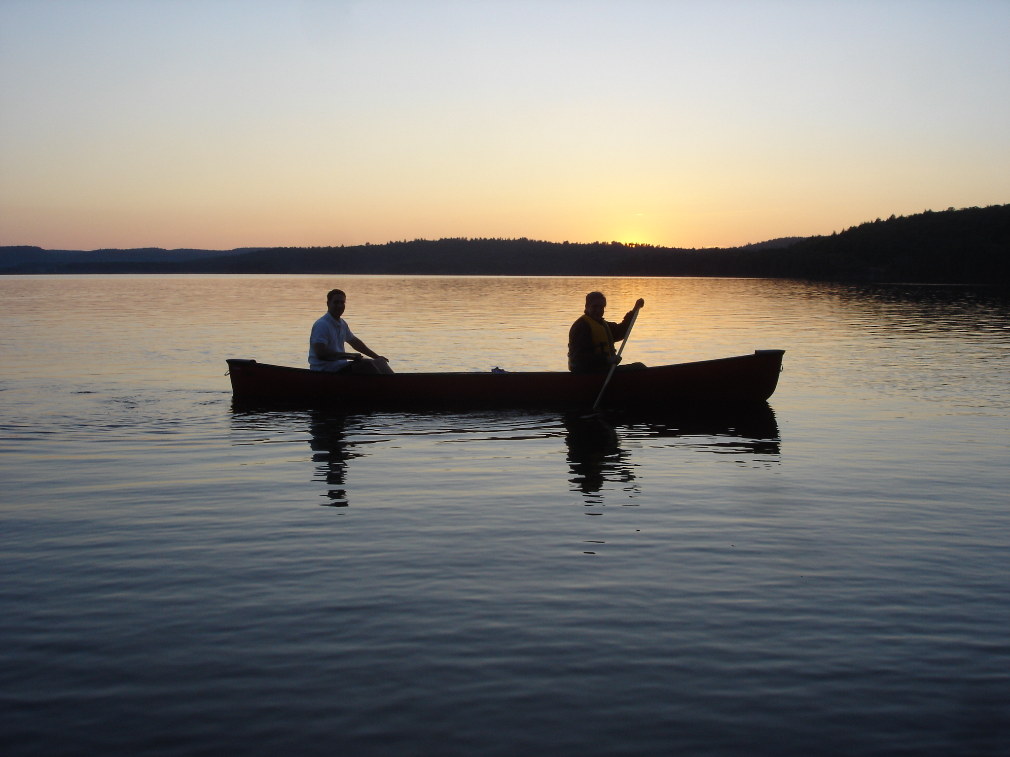 two men paddling in a canoe on a lake at dusk