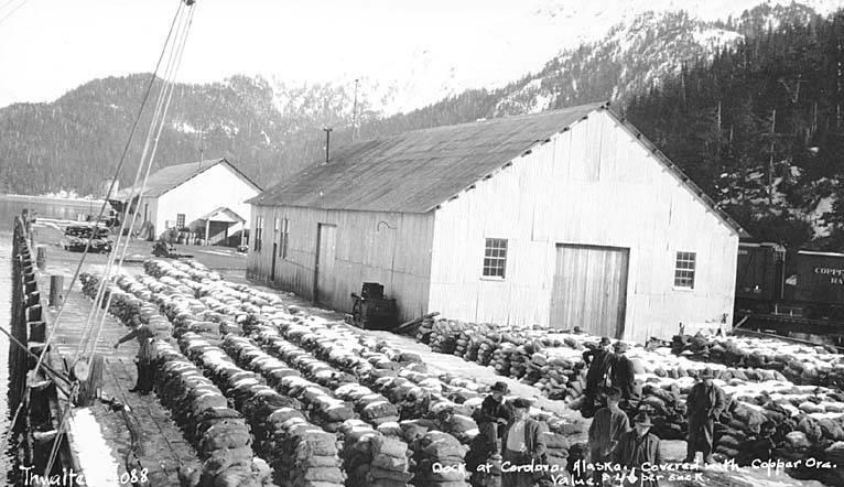 File:Copper ore cargo on dock at Cordova, ca 1912 (THWAITES 147).jpeg