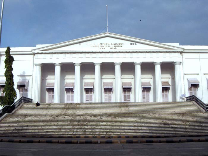 A white building with a triangular façade and wide stairs