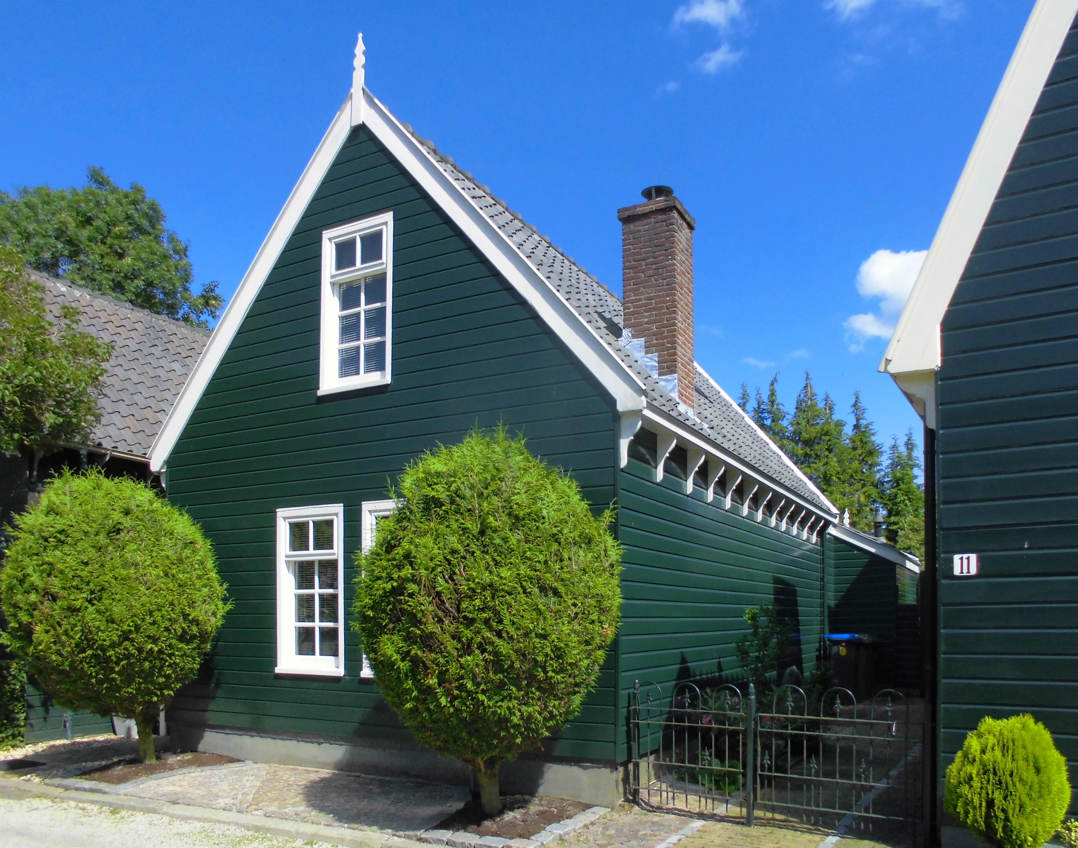 Houten huis met gerabatte wanden met zolderverdieping onder zadeldak met puntgevel met makelaar - Houten huis ...