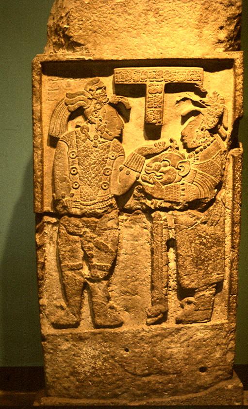 Linteau 26 du Temple 23 du site maya de Yaxchilan : Dame K'abal Xook tent un casque de jaguar à son mari le roi Itzamnaaj Balam III.
