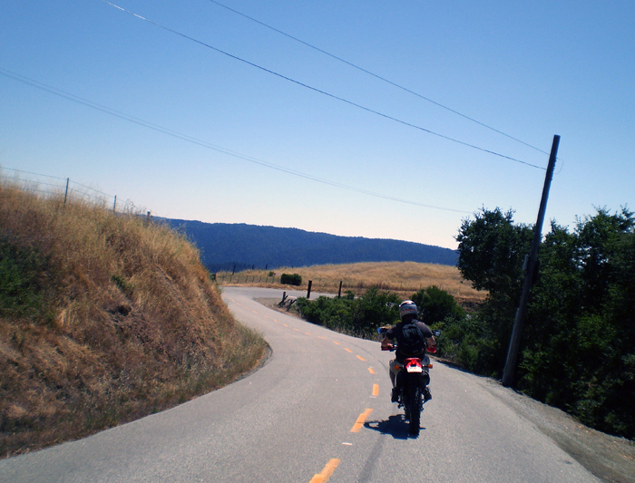 view of road on mountain spine of high chaparral and live oaks, motorcycle ahead, other ridges dark purple in the distance