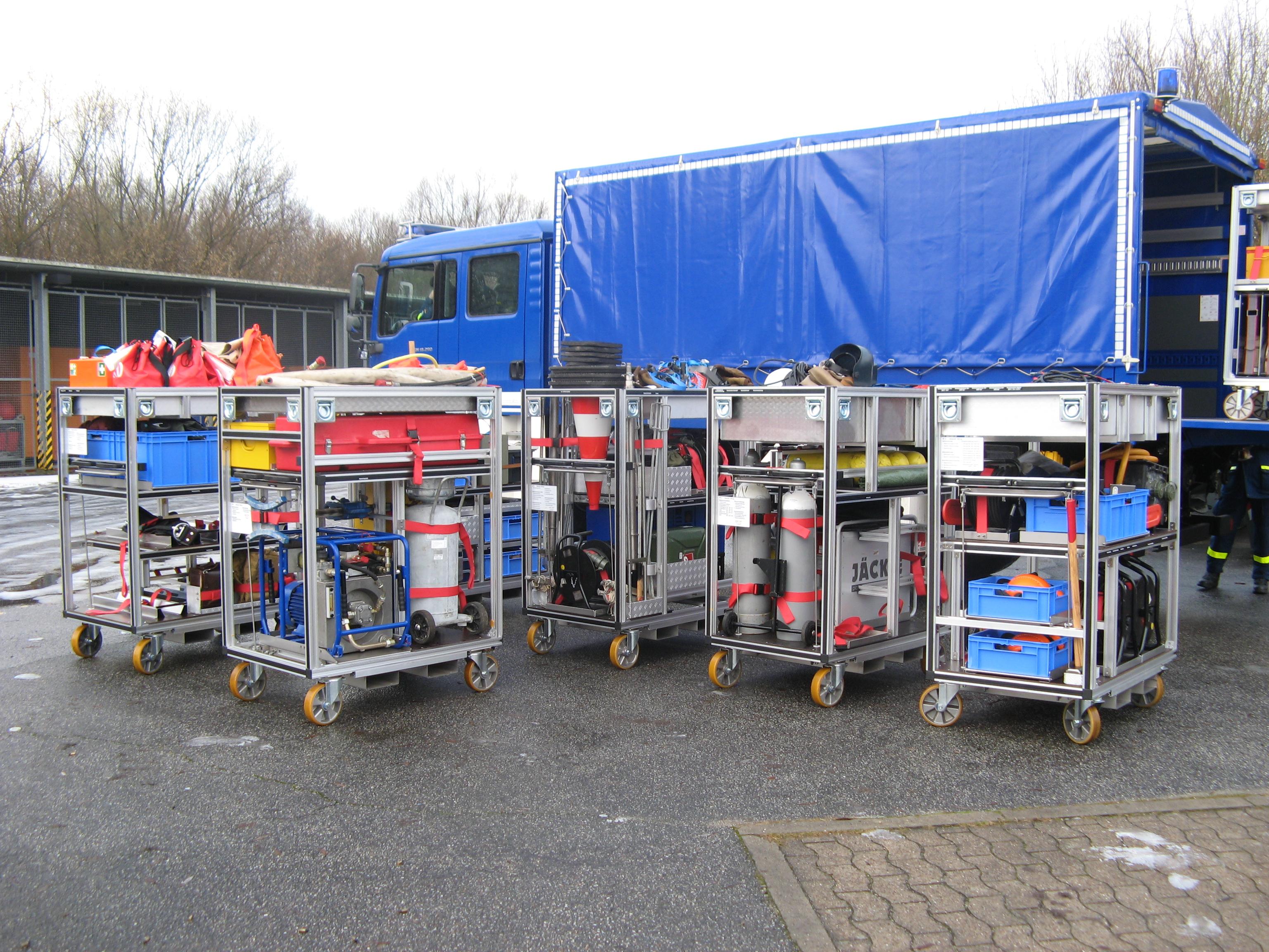 Mehrere Rollcontainer mit Ware und LKW im Hintergrund