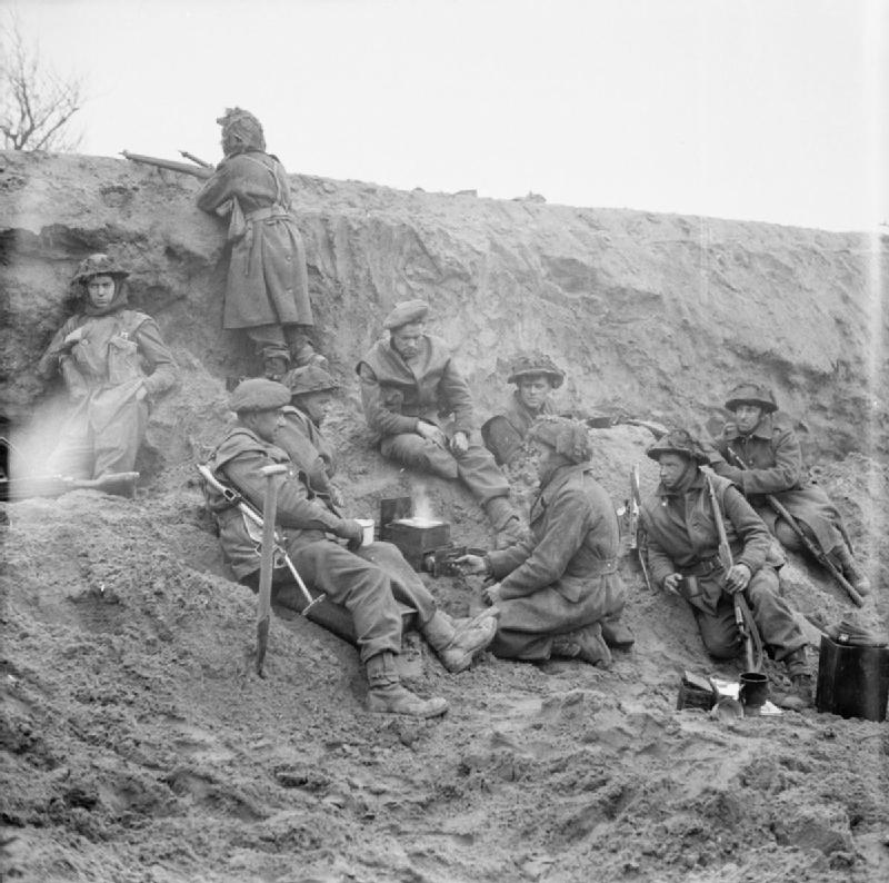 Infantry of the British Monmouthshire Regiment cook a meal in a forward position