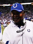 Color photograph of Jim Caldwell wearing a blue Indianapolis Colts hat and white sport shirt, headset around his neck, standing on football field sideline.