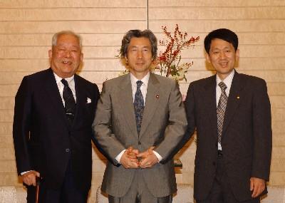 2002年10月11日、総理大臣官邸にて内閣総理大臣小泉純一郎(中央)、島津製作所分析計測事業部ライフサイエンスビジネスユニットライフサイエンス研究所主任田中耕一(右)と Wikipediaより