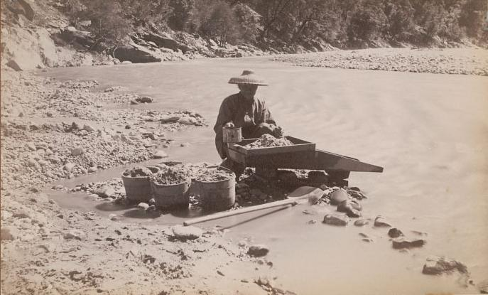 Chinese man mining along a river