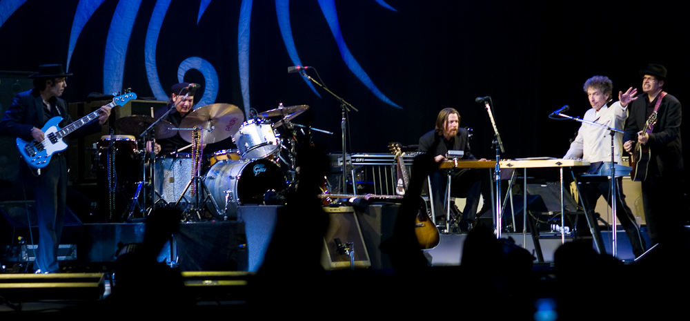 Dylan together with five members of his band onstage. Dylan, dressed in a white shirt and black pants, is second from right.