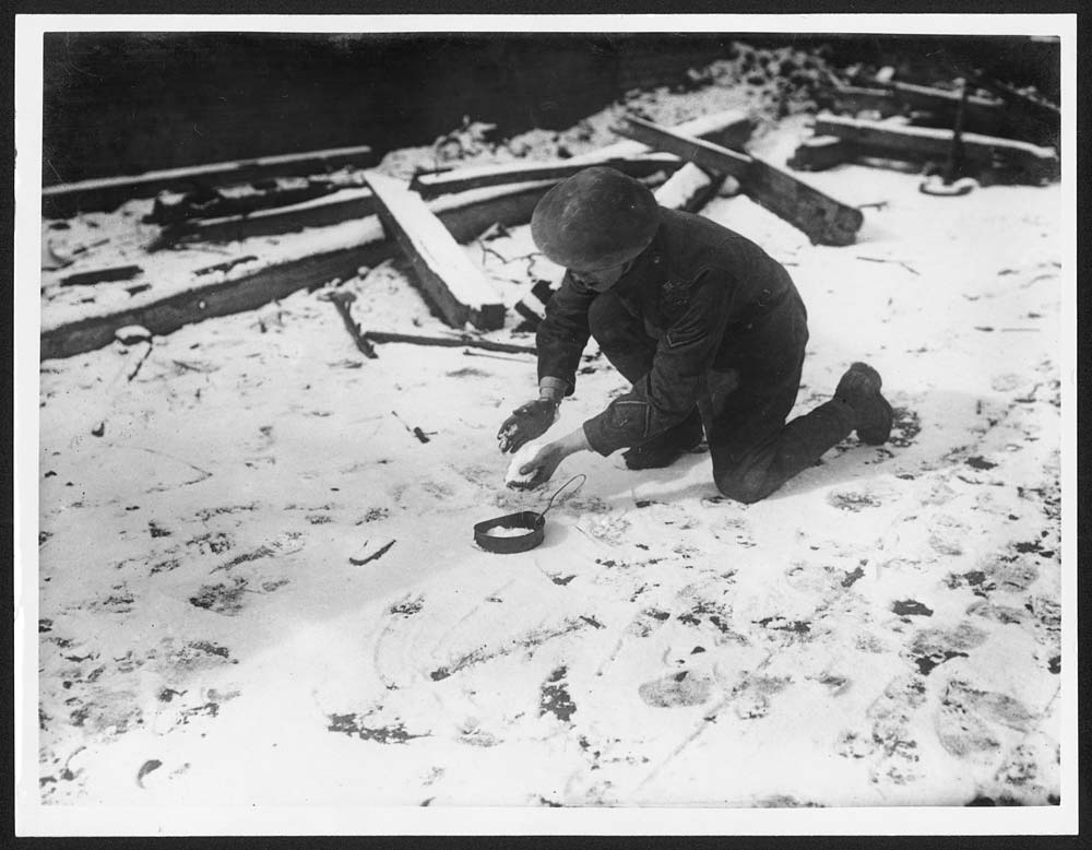 Soldier collecting snow to melt for water, Western Front. In this photograph, a British soldier is shown filling a small mess tin with snow. The original caption explains that he was about to melt the snow to get some water, as the Germans had poisoned the water supply in the area. This was a common tactic of the Germans when they were forced to retreat. It not only demoralised the Allies, but created practical difficulties for them.The letters RE on the soldier's left shoulder suggest he was a Royal Engineer. By his cuff he has a good conduct chevron and a single wound stripe. [Original reads: 'The ever resourceful Tommy. As the Huns have poisoned all water, Tommy makes snow answer his purpose.'] http://digital.nls.uk/74549290