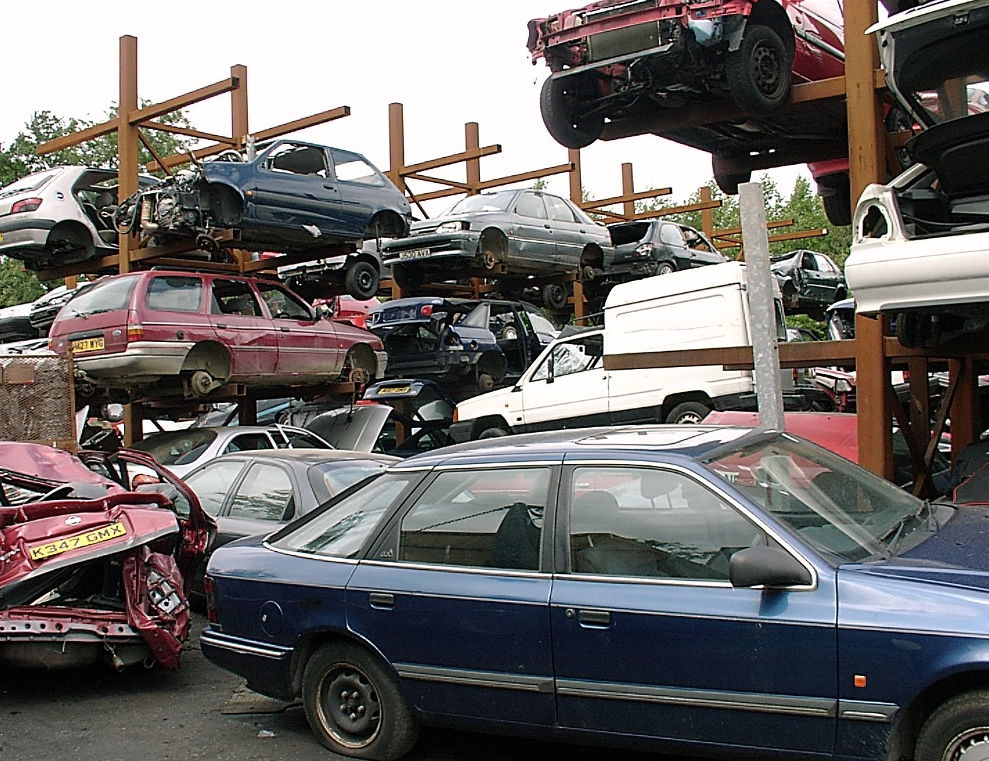 Vehicles stacked for dismantling at a scrap yard