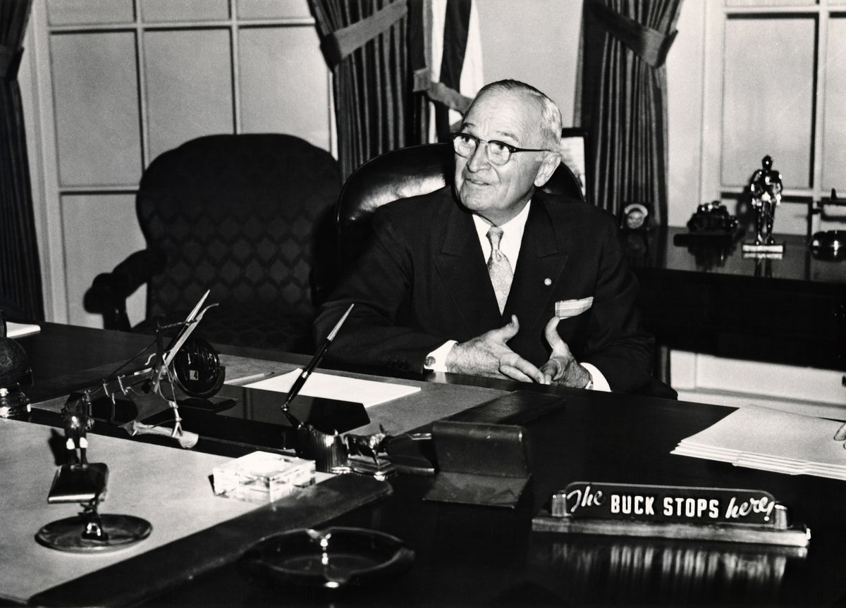 "Man in suit sitting behind desk with sign that says ""The buck stops here"""