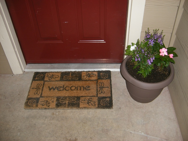 Welcome mat and flowers
