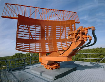 An ASR-9 airport surveillance radar antenna. The curving lower reflector is the primary radar, while the flat antenna on top is the secondary radar. Radio frequency energy enters and leaves the antenna via the two small orange horn feeds visible on the right foreground, and is guided to and from the radar processing circuitry through the black waveguides curving from the feeds into and down through the rotating central mount.