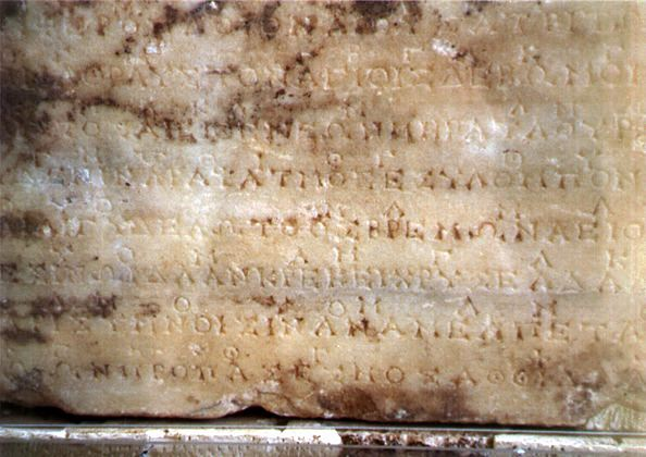 Photograph of the original stone at Delphi containing the second of the two hymns to Apollo. The music notation is the line of occasional symbols above the main, uninterrupted line of Greek lettering.