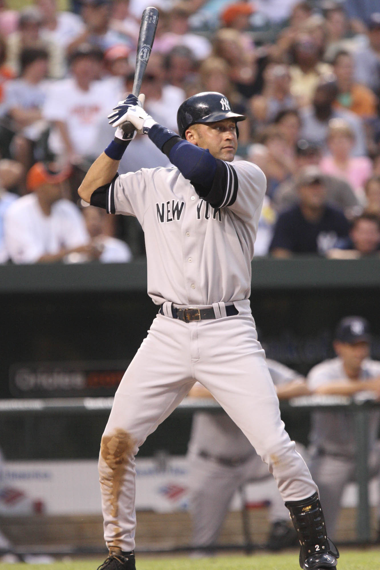 "A man in a grey baseball uniform with ""New York"" written on the front in navy letters and a navy helmet stands in a batting stance while holding a baseball bat."