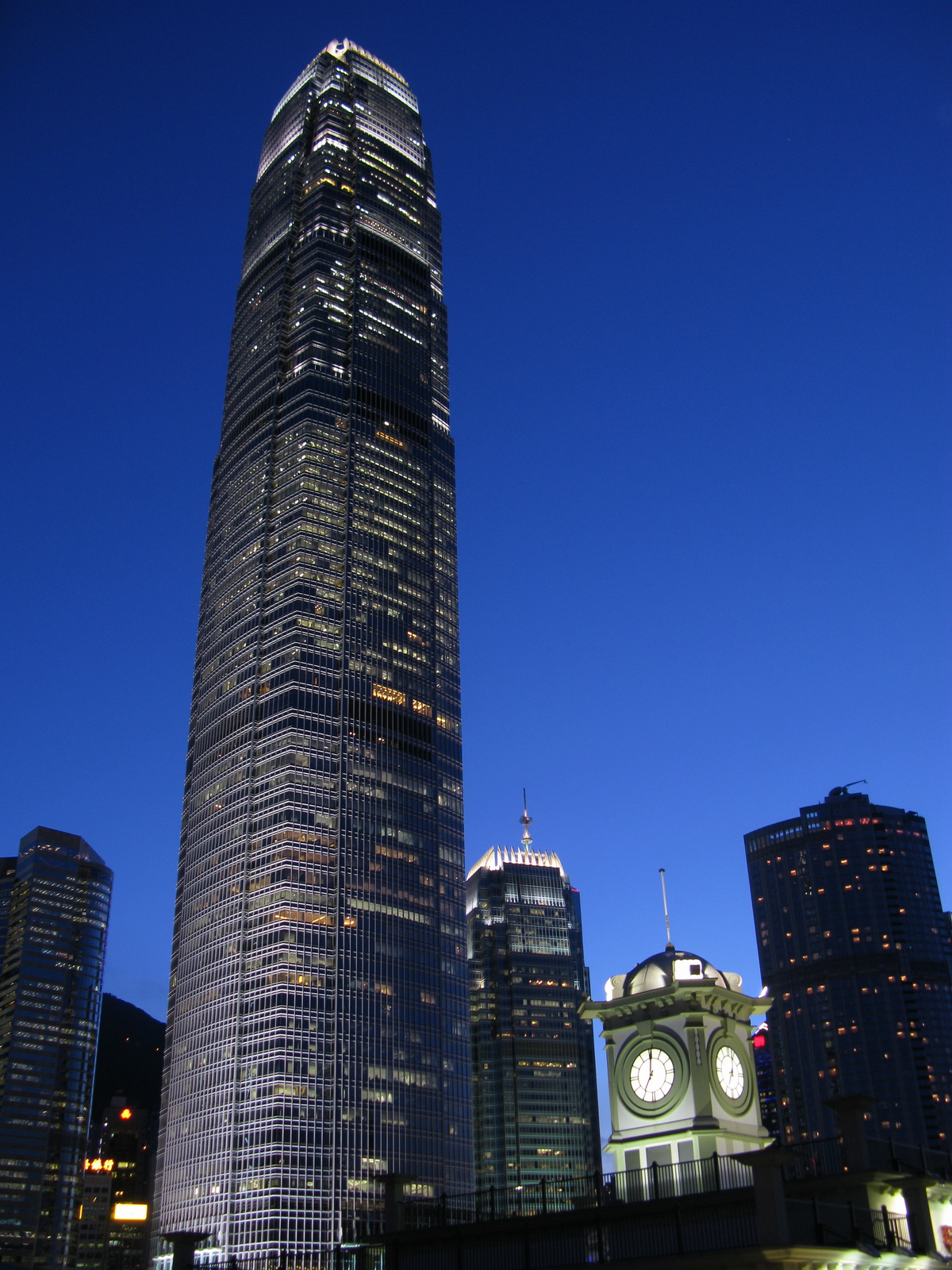 A brightly lit tall skyscraper at night.