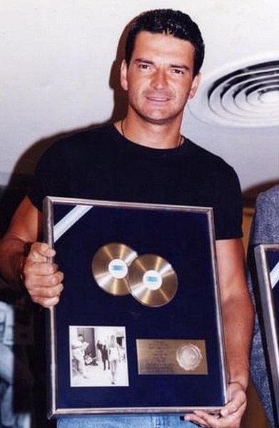 Ricardo Arjona recibiendo disco de platino por su álbum Sin daños a terceros en 1998.