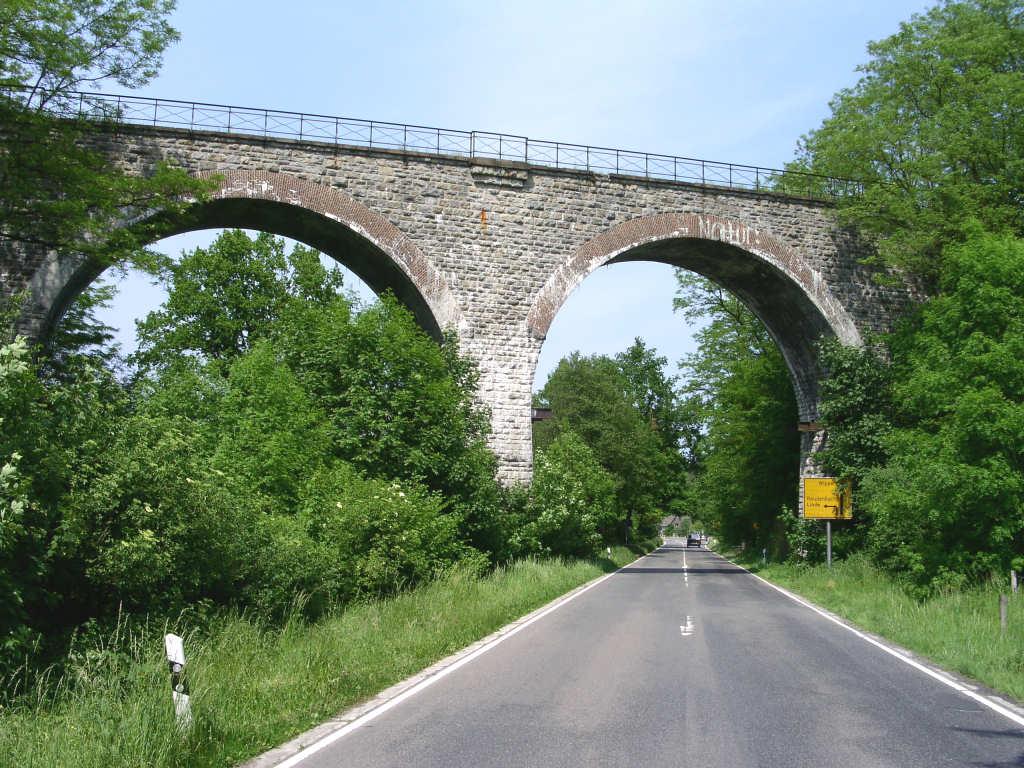 Eine steinerne Brücke mit Bögen, durch die eine Straße führt. Oben an der Brücke ist ein Brückengeländer.