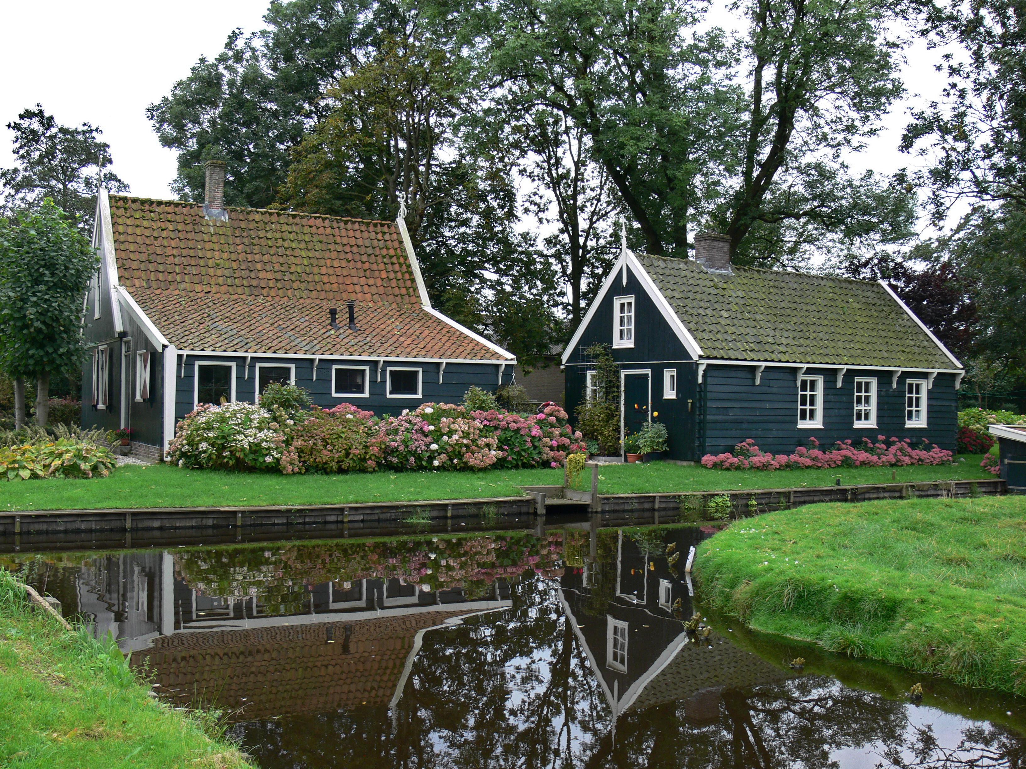 Houten huis onder met pannen gedekt zadeldak afhang aan de linkerzijde in watergang monument - Houten huis ...