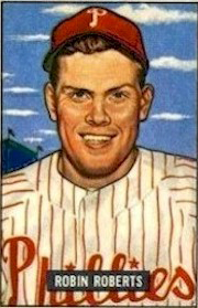 "A baseball card image if a smiling man wearinga white baseball jersey with red pinstripes and a red baseball cap; the caption on the card reads ""Robin Roberts"""