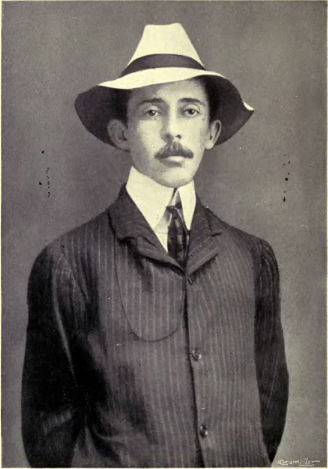 Santos-Dumont standing with his hands behind his back in a suit and hat
