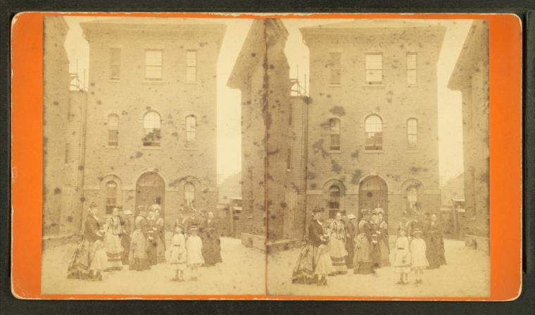 An old, faded picture of two three-storey buildings from between 1865 and 1885