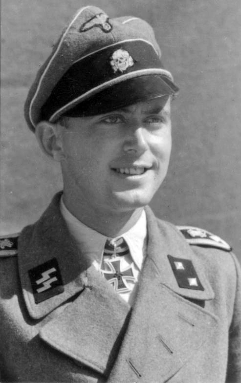 alt=A man wearing a military uniform, peaked cap and a neck order in the shape of a cross. His cap has an emblem in shape of a human skull and crossed bones.